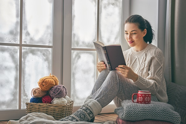 Ukrainian woman sitting by the window and reading her book wearing warm clothes