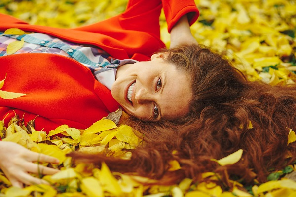 Young beautiful Ukrainian lady surrounded by autumn leaves with a smile
