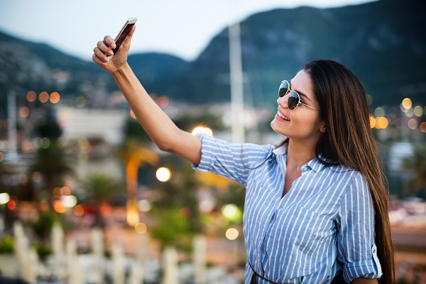 Happy young Ukrainian woman taking a selfie during her vacation with sunglasses on