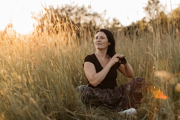 A young Ukrainian woman enjoying plaiting her hair in nature at the sunset