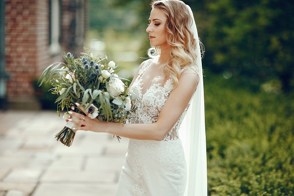 Elegant Ukrainian bride standing with a huge bouquet of flowers in the park