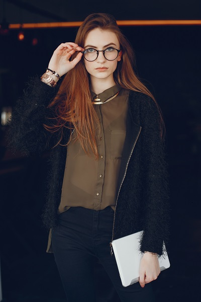 Stylish young Ukrainian businesswoman taking her glasses off in a cafe
