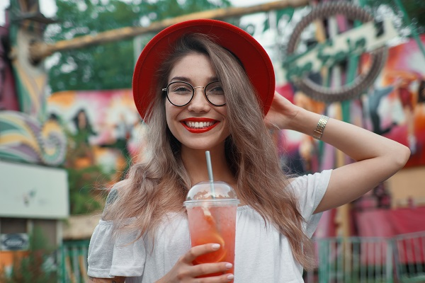 Cheerful young Ukrainian woman holding a drink while smiling at the camera