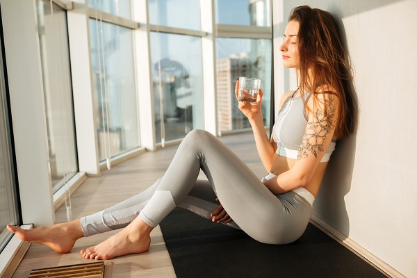 Pensive Ukrainian lady in a sporty top and leggings sitting on a yoga mat