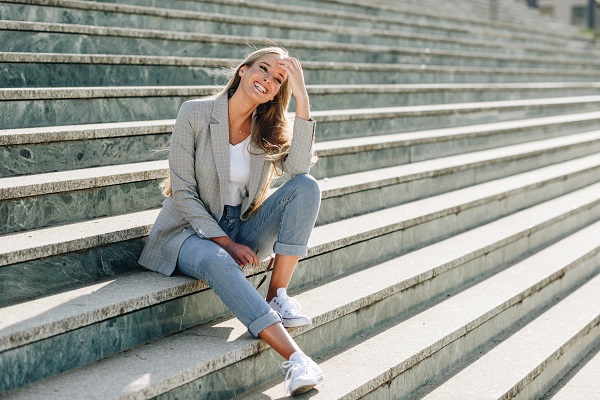 Beautiful young smiling Ukrainian girl sitting on steps wearing fashionable jeans