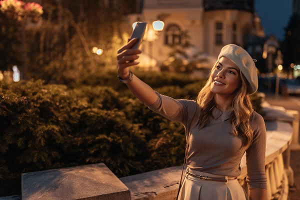 Smiling charming Ukrainian lady taking a photo of herself while walking in the evening all alone