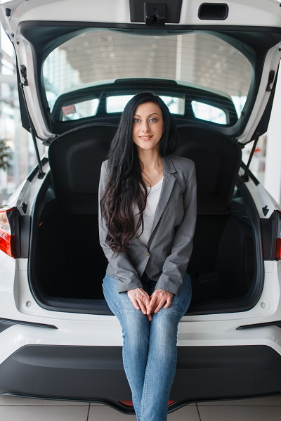 A photo of a curvy young Ukrainian woman sitting at the back of her new car posing for the camera